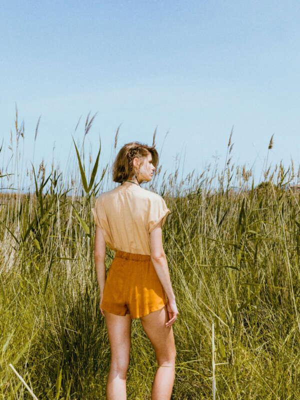 Beige t-shirt with orange shorts /the back side